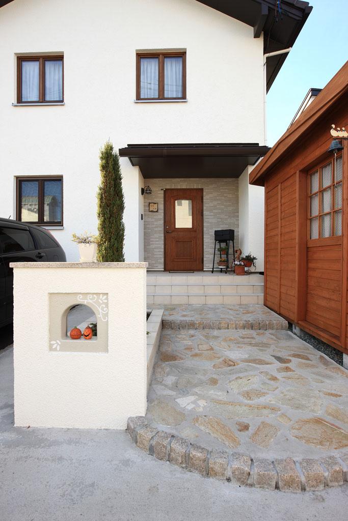 オフホワイトと木製ドア・窓枠がナチュラルな印象を与える外観