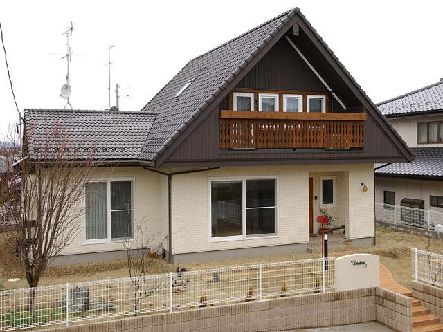 大きな三角屋根と木製のバルコニーがナチュラルな雰囲気のお住まい