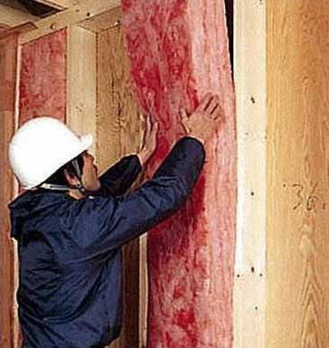 外壁の枠組材の間に断熱材を充填する様子